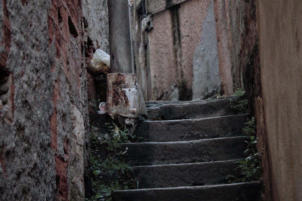 Alguns moradores improvisaram uma lata com cimento para segurar o poste que fica na escadaria com circulação continua de pedestres.