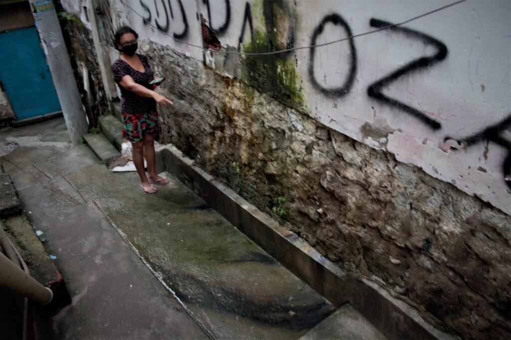 A parede externa está toda comprometida, oca e minando esgoto.